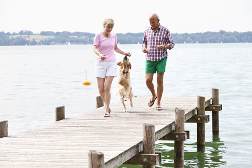 Germany, Bavaria, Starnberger See, Senior couple with Golden Retriever on jetty - MAEF01908