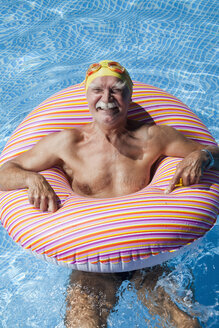 Austria, Senior man with floating tire in swimming pool, smiling, portrait - MAEF01893