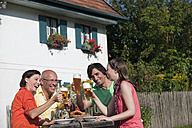 Germany, Bavaria, Four persons drinking beer in the garden, having fun, portrait - WESTF13269