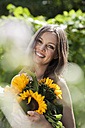 Germany, Bavaria, Woman holding bunch of sunflowers, smiling, portrait - WESTF13248