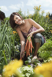 Germany, Bavaria, Woman holding bunch of carrots in garden, smiling, portrait - WESTF13233