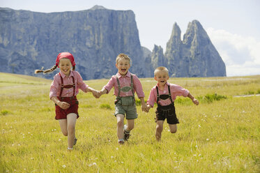 Italy, Seiseralm, Three children (4-5), (6-7), (8-9) running in field - WESTF13385