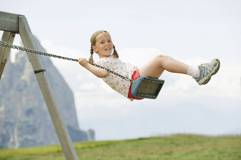 Italy, Seiseralm, Girl (6-7) sitting on swing, portrait - WESTF13370
