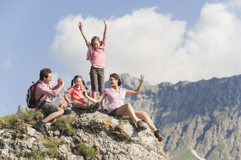 Italy, South Tyrol, Family sitting on rock, man taking photo - WESTF13712