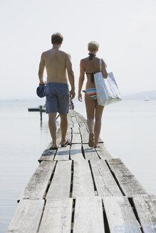 Germany, Bavaria, Young couple wearing swimwear walking on jetty, rear view - LDF00801
