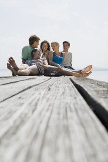 Germany, Bavaria, Ammersee, Young people sitting on jetty, laughing, portrait - LDF00795