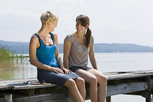 Germany, Bavaria, Ammersee, Young women sitting on jetty - LDF00792