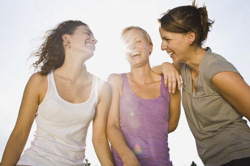 Germany, Bavaria, Three young women side by side, laughing, portrait, close-up - LDF00783