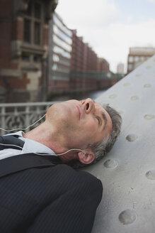 Germany, Hamburg, Businessman lying on back, using MP3 player - WESTF13851