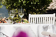 Italy, South Tyrol, Laid table, with mixed salad on plates and two glasses with white wine - WESTF13780