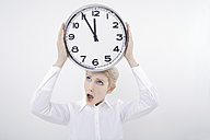 Woman holding clock with open mouth - TCF01276