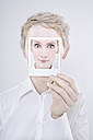 Woman holding polaroid picture in front of her face - TCF01267