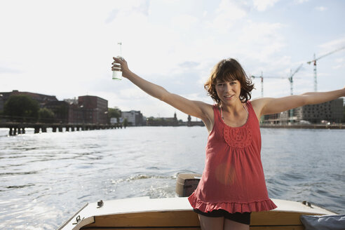 Germany, Berlin, Young woman on motor boat, arms outstretched - VVF00059