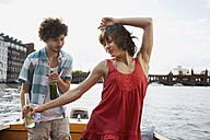 Germany, Berlin, Young couple on motorboat, man looking at woman dancing, portrait - VVF00053