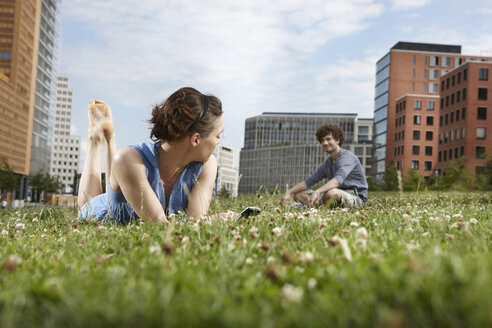 Germany, Berlin, Young woman lying in meadow holding mobile phone, man in background - VVF00035