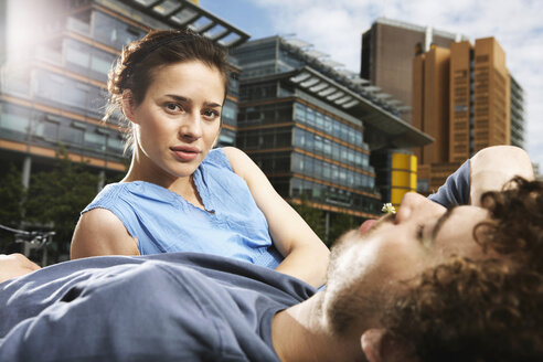 Germany, Berlin, Young couple lying in meadow, high rise buildings in background - VVF00032