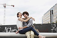 Germany, Berlin, Young couple in front of new building, cranes in background - VVF00020