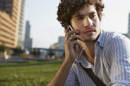 Germany, Berlin, Young man using mobile phone, portrait - VVF00008