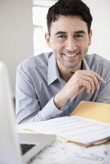 Businessman in office holding ballpen, smiling, portrait - JRF00158