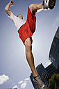 Germany, Berlin, Young man jumping in air, low angle view - SKF00110