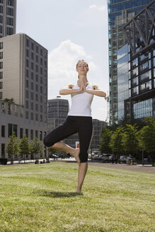 Germany, Berlin, Young woman exercising yoga, eyes closed - SKF00104