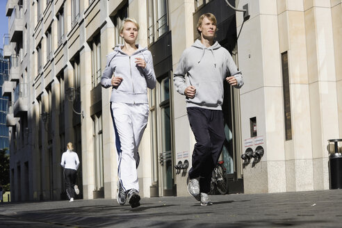 Germany, Berlin, Young couple jogging together - SKF00068