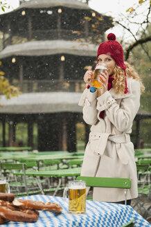 Germany, Bavaria, English Garden, Woman drinking beer in beer garden - WESTF14089