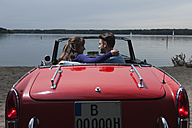 Germany, Berlin, Lake Wannsee, Young couple in cabriolet embracing, side view, portrait - WESTF13987