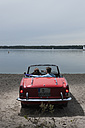 Germany, Berlin, Lake Wannsee, Young couple in cabriolet looking at lake, rear view - WESTF13984
