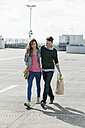Germany, Berlin, Young couple walking on deserted parking level - WESTF13951