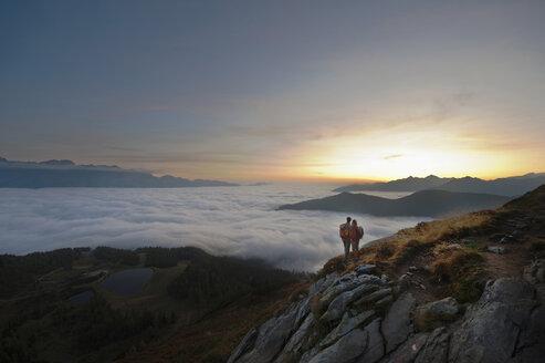Austria, Steiermark, Reiteralm, Hikers admiring view over clouds - HHF03118