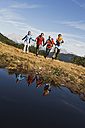 Austria, Salzburger Land, Four hikers running across field - HHF03115