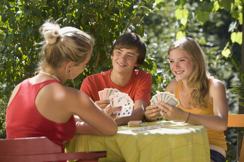 Austria, Salzburger Land, Teenagers  (14-15) playing cards in garden - WWF01117