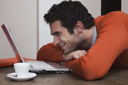 Man with coffee cup, smiling at laptop - WESTF14409