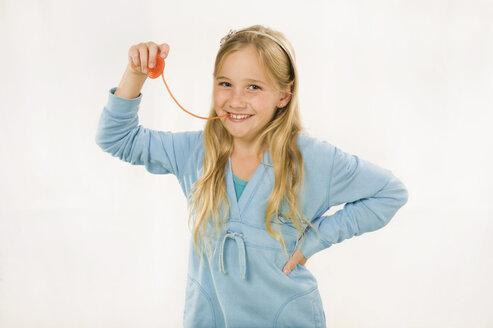 Girl (8-9) eating wine gum, smiling, portrait - RNF00236