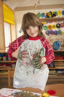 Germany, Boy (6-7) fingerpainting in nursery, portrait - RNF00185