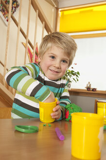 Germany, Boy (3-4) in nursery playing with modeling clay, smiling, portrait - RNF00146