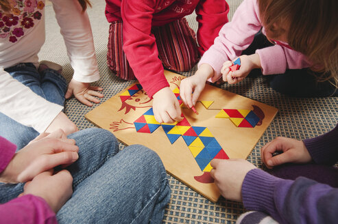 Germany, Five children playing a learning game together, close-up, mid section - RNF00116