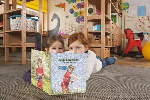Germany, Two girls (4-5), (6-7) in nursery lying on carpet reading a book, portrait - RNF00104
