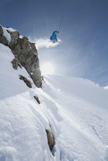 Austria, Arlberg, Man skiing downhill, doing jump, low angle view - MIRF00030