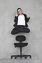 Businesswoman using mobile phone floating above chair, elevated view - BAEF00075