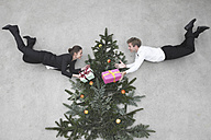Businessman and businesswoman flying in front of christmas tree, holding presents, smiling, portrait, elevated view - BAEF00066