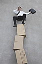Businessman balancing on stack of cardboard boxes, using mobile phone, elevated view - BAEF00063