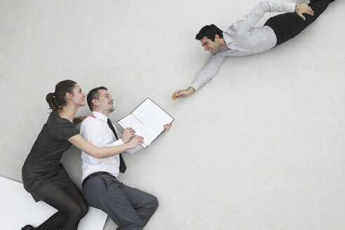 Three business people, businessman signing contract, elevated view - BAEF00054