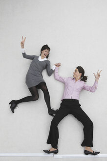 Two businesswomen gesturing, laughing, portrait, elevated view - BAEF00042