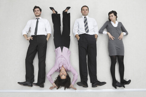 Four business people side by side, woman doing handstand, portrait, elevated view - BAEF00036