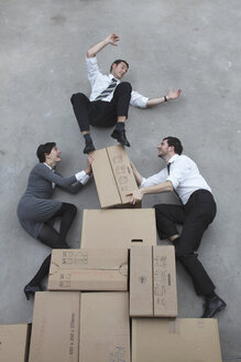 Three business people balancing on cardboard boxes, smiling, portrait, elevated view - BAEF00033