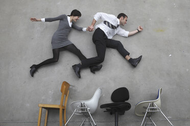 Businessman and Businesswoman hand in hands, jumping over chairs, side view, elevated view - BAEF00024