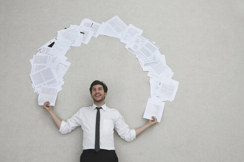 Businessman juggling with documents, smiling, portrait, elevated view - BAEF00018