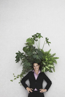 Businesswoman with Foliage Plants, smiling, portrait, elevated view - BAEF00015